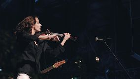 Cheerful and smiling girl violinist plays on stage. Cool and professional musician. stock video footage