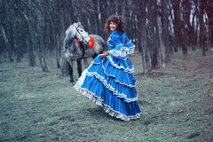 Cheerful smiling girl walking with a horse Royalty Free Stock Photos
