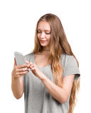 A cheerful, smiling and happy girl with charming long blond hair is holding a phone, isolated on a white background. stock photos