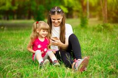 Cheerful smiling happy mother and her little daughter are sitting on green grass in summer park royalty free stock photos
