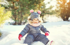 Cheerful smiling little child playing on snow in winter Stock Photos