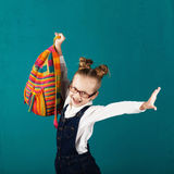 Cheerful smiling little girl with big backpack jumping and havin Stock Photos