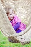 Cheerful smiling little girl enjoy in hammock outdoor. Happy chi Stock Photo