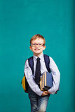 Cheerful smiling little kid with big backpack. Book, school, kid. little student holding books. Cheerful smiling little kid with big backpack against chalkboard stock photo