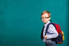 Cheerful smiling little kid with big backpack. School, kid, rucksack. little Boy in eyeglasses. Cheerful smiling little kid with big backpack against chalkboard stock photo
