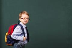 Cheerful smiling little kid with big backpack. School, kid, rucksack. little Boy in eyeglasses. Cheerful smiling little kid with big backpack against chalkboard stock images