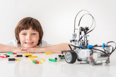 Cheerful smiling male child glancing at robot Royalty Free Stock Photo