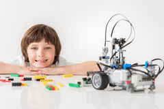 Cheerful smiling male child glancing at robot royalty free stock photos
