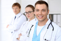 Cheerful smiling male doctor with medical staff at the hospital.  Royalty Free Stock Photo