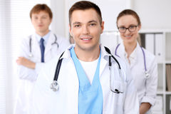 Cheerful smiling male doctor with medical staff at the hospital.  Royalty Free Stock Photography