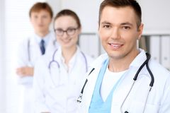 Cheerful smiling male doctor with medical staff at the hospital.  Royalty Free Stock Images