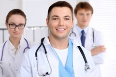 Cheerful smiling male doctor with medical staff at the hospital.  Stock Photo