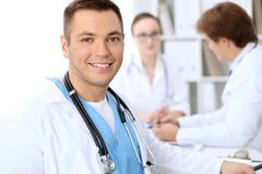 Cheerful smiling male doctor with medical staff at the hospital.  Stock Images