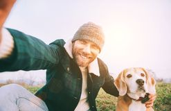 Cheerful smiling Man takes selfie photo with his best friend beagle dog during walking. Human and pets concept image