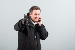 Cheerful smiling man in winter clothes talking on cellphone Stock Photos