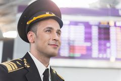 Cheerful smiling military man looking up. Happy male pilot is glancing forward with bright dreamy smile. Portrait. Copy space on right side Stock Photography