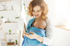 Cheerful smiling mother drinks cocoa and texting her beloved husband while small son dozing in baby slim. Atmosphere of Royalty Free Stock Photos