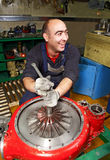 Cheerful, smiling Muslim turbocharger impeller repairs in factor Royalty Free Stock Images