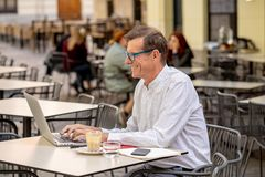 Cheerful smiling old man working on computer while having coffee in terrace coffee shop city outdoors in seniors using modern stock image