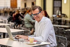 Cheerful smiling old man working on computer while having coffee in terrace coffee shop city outdoors in seniors using modern stock photography