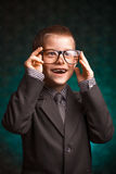 Cheerful smiling pupil on a green background. Royalty Free Stock Photos