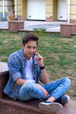 Cheerful smiling and sitting teenage boy talking by phone. Stock Image