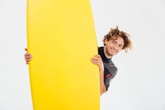 Cheerful smiling sportsman looking out of surfboard. Cheerful smiling sportsman looking out of the surfboard isolated on the white background Stock Image