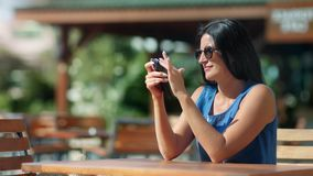 Cheerful smiling tanned woman using smartphone at outdoor cafe during summer vacation