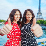 Cheerful smiling twin sisters showing thumbs up in front of Eiffel Tower, Paris Stock Images