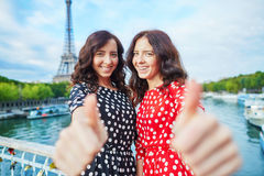 Cheerful smiling twin sisters showing thumbs up Stock Photography
