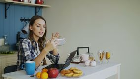 Cheerful smiling woamn talking online video chat using smartphone in the kitchen at home. In the morning stock video footage