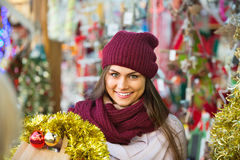 Cheerful smiling  woman choosing Christmas decoration Royalty Free Stock Photo