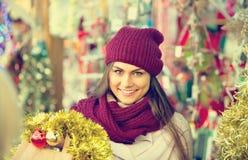 Cheerful smiling  woman choosing Christmas decoration Stock Photos