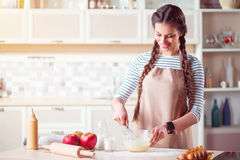 Cheerful smiling woman cooking in the kitchen Stock Image