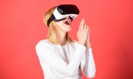 Cheerful smiling woman looking in VR glasses. Woman using VR device. Person with virtual reality helmet isolated on red. Background. Cyber sport stock photos