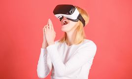 Cheerful smiling woman looking in VR glasses. Woman using VR device. Person with virtual reality helmet  on red. Background. Cyber sport stock photos
