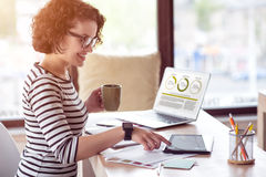 Cheerful smiling woman sitting at the table. Stay in positivity. Pleasant delighted beautiful woman drinking coffee and using laptop while sitting at the table stock photo