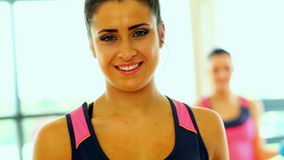 Cheerful smiling women lifting dumbbells. Standing in fitness hall stock video
