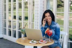 A cheerful smiling young girl is dressed in stylish casual jeans. talking to someone on the phone, sitting in a cafe. Ordered drinks and desserts. A woman came royalty free stock photos
