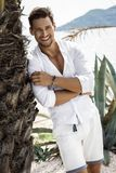 Cheerful smiling young male model. Wearing white shirt in summer scenery royalty free stock images