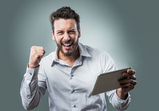Cheerful smiling young man with tablet Royalty Free Stock Image