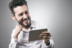 Cheerful smiling young man with tablet Stock Image