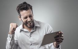 Cheerful smiling young man with tablet Stock Photos