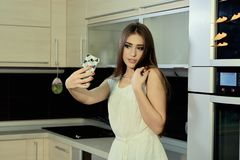 Cheerful smiling young white skin female with long brunette hair posing on the kitchen, makes selfie on the smartphone royalty free stock images