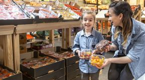 Cheerful smiling young woman with little daughter buying globe tomatoes at the market royalty free stock images