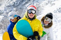 Cheerful snowboarders. Portrait of three happy young men with snowboards in googles Stock Image