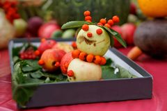 Cheerful snowman with apples and ashberry. royalty free stock photography