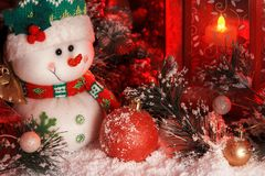 Cheerful snowman and Christmas balls are covered with snow in the light of a red lantern on the background of New Year`s scenery Royalty Free Stock Photos