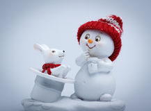 Cheerful snowman shows tricks Stock Images