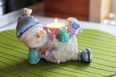 Cheerful snowman skier. Candlestick. Cheerful snowman skier. Candlestick with burning candle Stock Images